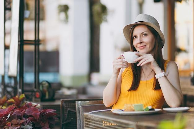 Donna in una caffetteria all'aperto di strada seduta al tavolo con un cappello giallo con una tazza di cappuccino, torta, rilassante nel ristorante durante il tempo libero