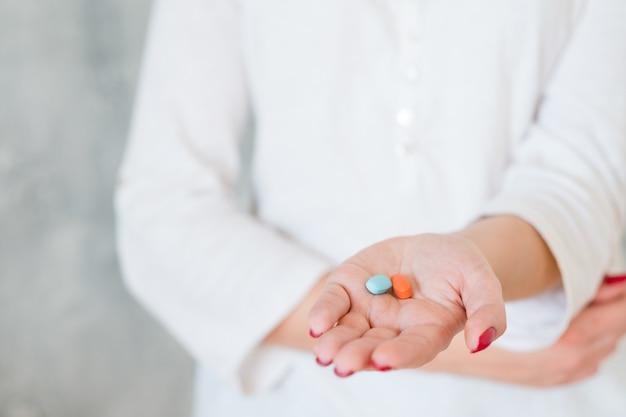 Mano tesa della donna con due pillole colorate che tengono la mano sulla pancia. farmaci antidolorifici e problemi di salute