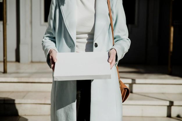 Donna in soprabito che porta una scatola bianca davanti a un edificio