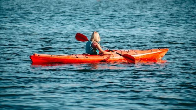 Donna che rema un kayak rosso nel fiume durante il giorno