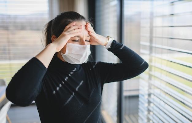 Donna che soffre di mal di testa e maschere facciali in casa, concetto di virus corona.