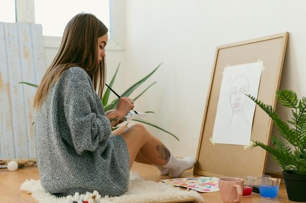 Pittore della donna che si siede sul pavimento