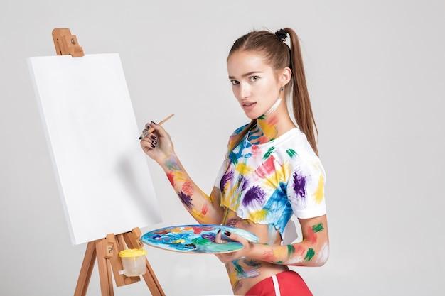 La pittrice sporca di vernice colorata disegna su tela