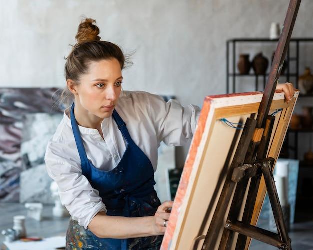 Donna che dipinge su tela a medio raggio