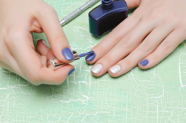 Donna che dipinge i suoi chiodi nel colore blu