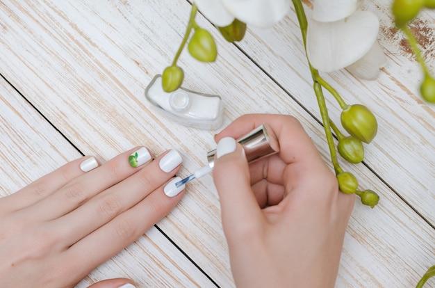 Donna che dipinge i suoi chiodi nel colore bianco.