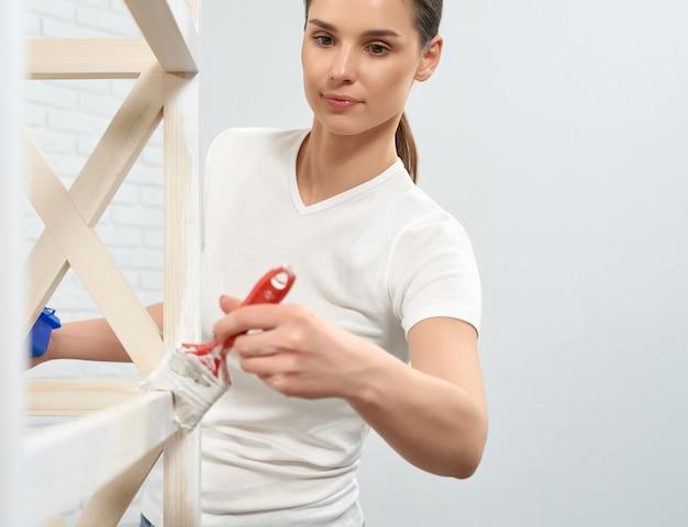 Donna che dipinge tavola di legno con pennello e colore bianco