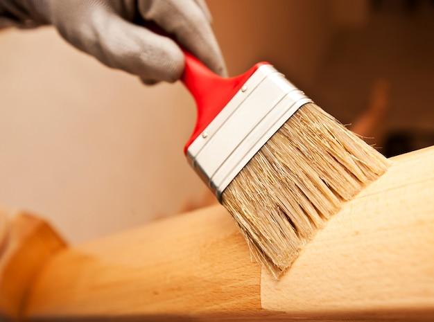 La donna dipinge una tavola di legno di vernice a pennello