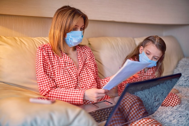 Donna in pigiama con notebook e documenti che lavorano da casa che indossa la maschera protettiva mentre suo figlio, figlia che gioca ai giochi della console del computer