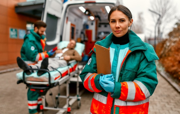 Una donna paramedica in uniforme è in piedi con una scheda paziente davanti a un'ambulanza e il suo collega in piedi vicino alla barella di un paziente.