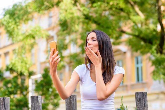 Una donna in un parco che fa un selfie con il suo smartphone