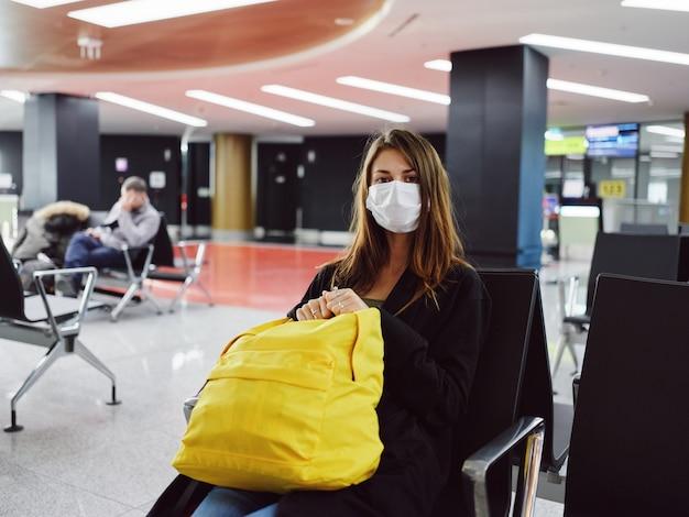 Passeggero donna che indossa una maschera medica all'aeroporto in attesa gialla