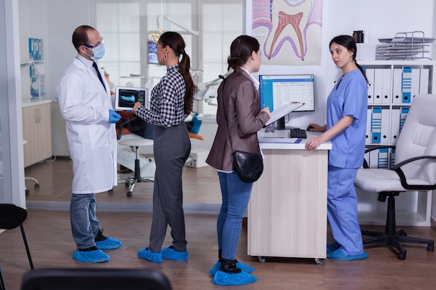 Paziente donna che chiede informazioni all'addetto alla reception dentale che riempie i denti del trattamento sanitario