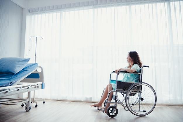 Paziente della donna in camicia verde che si siede sulla sedia a rotelle della clinica dell'ospedale nella stanza del paziente.
