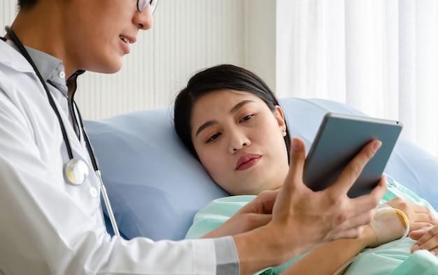 Paziente della donna sul letto di ospedale guardando la tavoletta digitale mentre il medico maschio spiega e discute i suoi problemi di salute