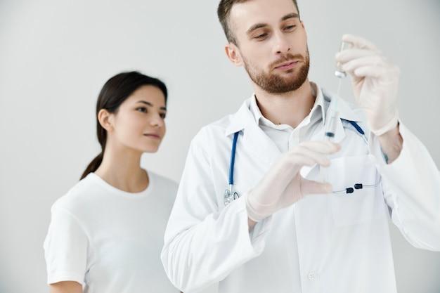 Paziente della donna che esamina la siringa nel fondo chiaro di coronavirus di vaccinazione della mano del medico. foto di alta qualità
