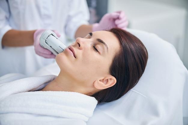 Paziente donna che si rilassa durante il trattamento facciale ad ultrasuoni condotto da un'estetista in guanti sterili