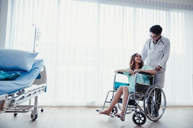 Paziente della donna sulla sedia a rotelle nella stanza del paziente con cura del medico.
