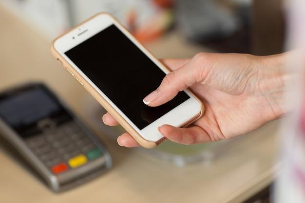Donna che paga la bolletta tramite smartphone utilizzando la tecnologia nfc in ristorante, caffetteria, bar