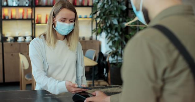 Donna che paga il caffè utilizzando la tecnologia nfc con telefono e carta di credito, pagamento senza contatto con studentessa donna dopo la pandemia di quarantena del coronavirus.