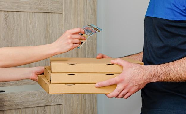 La donna paga i soldi per la consegna della pizza. concetto di ordine alimentare