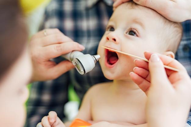 Il pediatra della donna sta esaminando il piccolo bambino in clinica. controllo della gola del bambino.