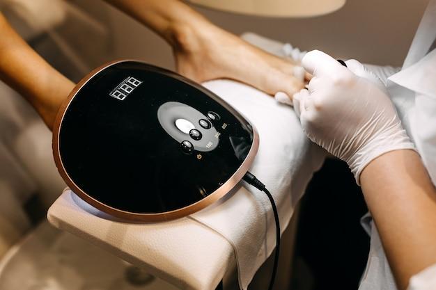 Donna in una procedura di pedicure, utilizzando la lampada a led uv gommalacca
