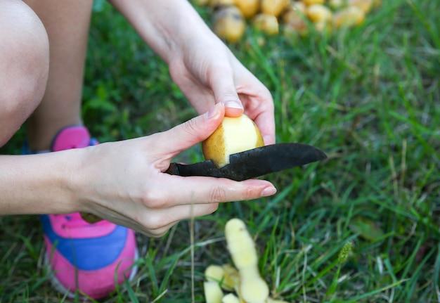 La donna sbuccia le patate. pranzo fatto in casa all'aperto. vibrazioni estive.