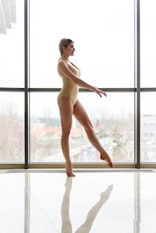 Donna che esegue una danza contro una finestra