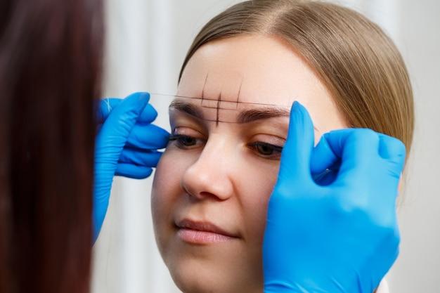 Una truccatrice permanente donna disegna uno schizzo delle sopracciglia sul viso del suo cliente.