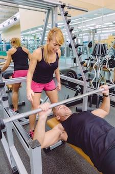 Istruttore personale della donna che grida all'uomo del muscolo in un allenamento della panca con bilanciere sul centro fitness motivazione nel concetto di formazione.