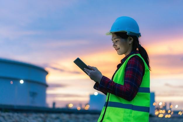 Ingegnere petrolchimico donna che lavora con tavoletta digitale