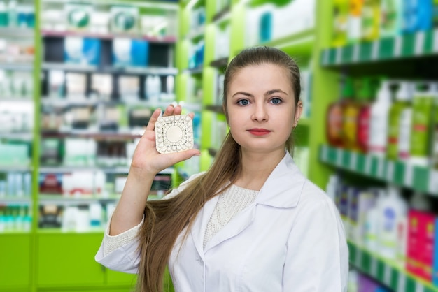 Farmacista della donna che mostra le pillole della bolla in farmacia