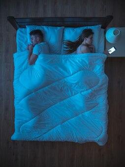 Il telefono della donna sul letto vicino al marito. notte. vista dall'alto