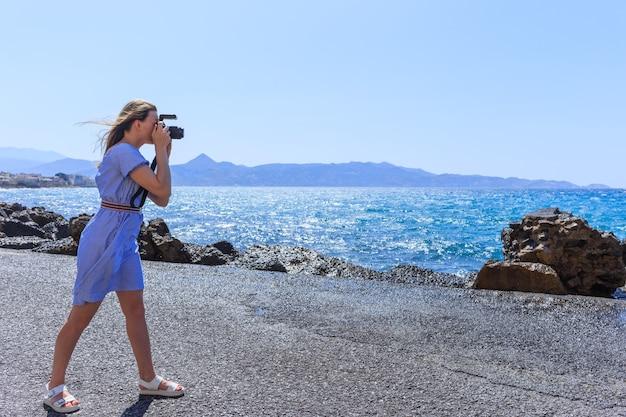 Fotografo donna fotografo naturalista che riprende il mare. concetto di viaggio.