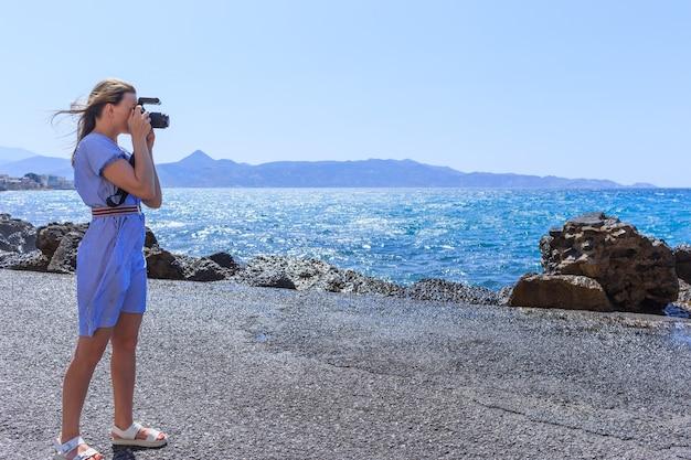 Fotografo donna fotografo naturalista che riprende il mare.