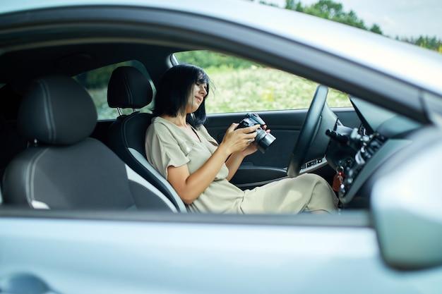 Fotografa donna seduta in macchina e guardando la foto sulla fotocamera, donna di viaggio scatta foto, spazio per il testo