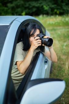 Fotografa donna seduta in macchina e fotografando un paesaggio di campo di fiori, donna di viaggio scatta foto, spazio per il testo