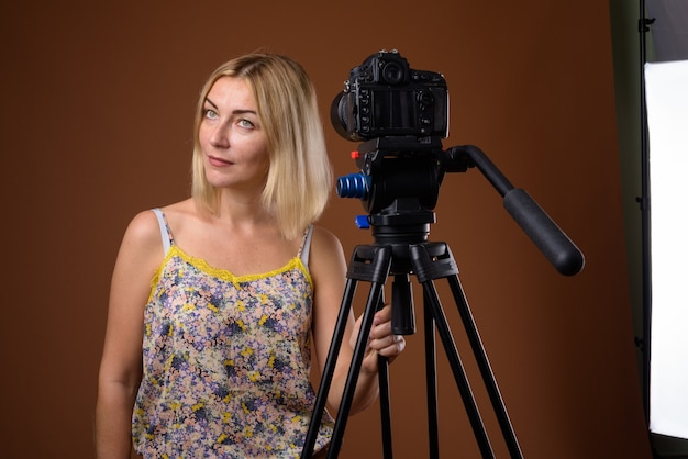 Fotografo di donna con fotocamera dslr in treppiede in studio