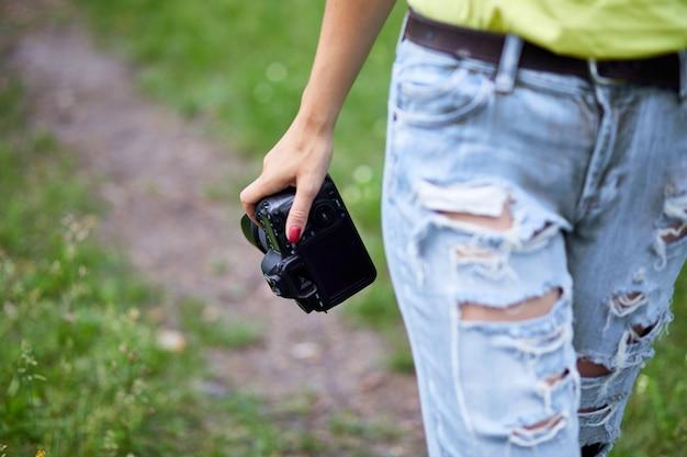 Fotografa donna con una macchina fotografica in mano all'aperto, giornata mondiale del fotografo, hobby creativo, spazio copia, posto per testo, concetti fotografici professionali.