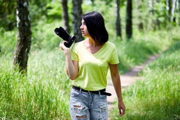 Fotografo donna con una macchina fotografica in mano all'aperto, giornata mondiale del fotografo.