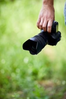 Fotografo di donna con una macchina fotografica in mano all'aperto