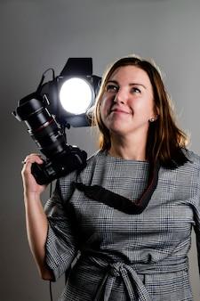 Fotografa donna con una fotocamera reflex in studio alza lo sguardo sognante e sorride ai suoi sogni