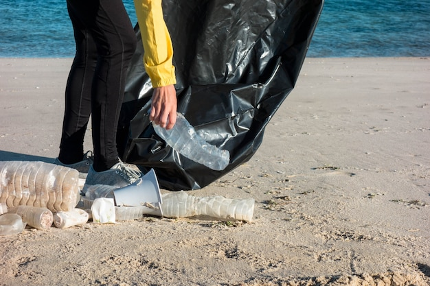 Donna che raccoglie spazzatura e plastica che pulisce la spiaggia con un sacco della spazzatura. attivista ambientalista volontario contro il cambiamento climatico e l'inquinamento degli oceani.