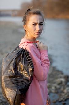 Donna che raccoglie spazzatura e plastica che pulisce la spiaggia con un sacco della spazzatura. attivista ambientalista volontario contro il cambiamento climatico e l'inquinamento dei fiumi.