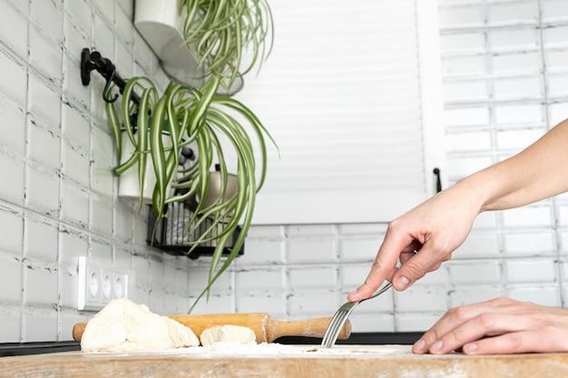 Donna che perfora la pasta con una forchetta per la cottura alla cieca