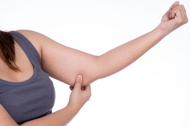 Donna che pizzica la pelle flaccida grassa del braccio isolata su fondo bianco