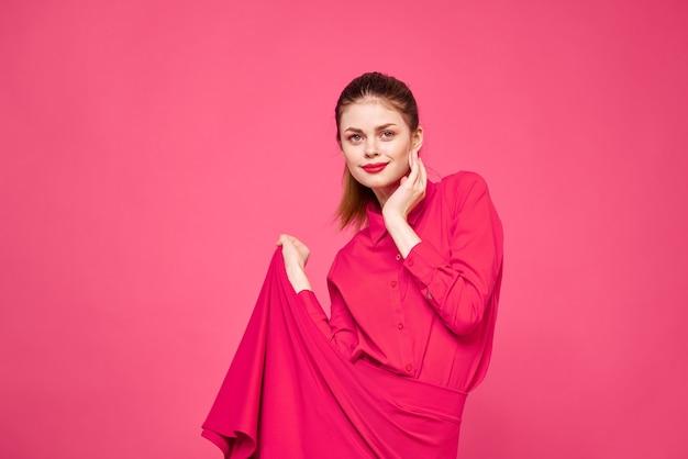 Donna su uno sfondo rosa in abiti alla moda e modello di acconciatura trucco luminoso
