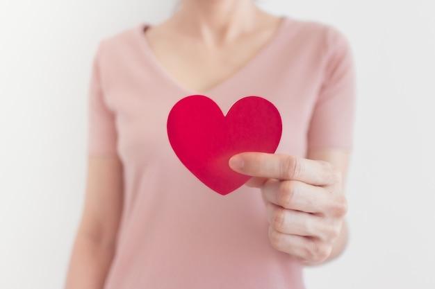 La donna in abito rosa mostra la forma del cuore nel concetto di amore e san valentino.