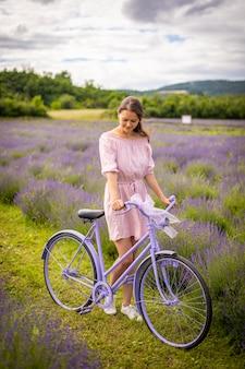 Donna in abito rosa con bicicletta retrò nel campo di lavanda repubblica ceca